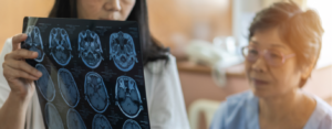 Woman looks at scans of her brain that her doctor holds up and explains