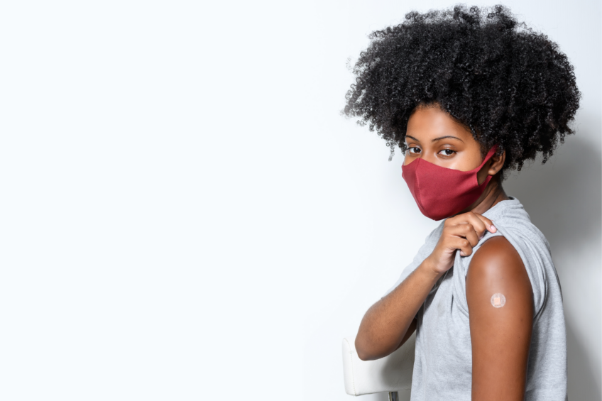 Young Black woman wearing a face mask shows off her arm, bandaged after getting a covid vaccine