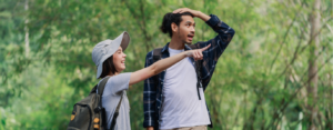 Smiling couple hikes in the woods and points at something out of frame
