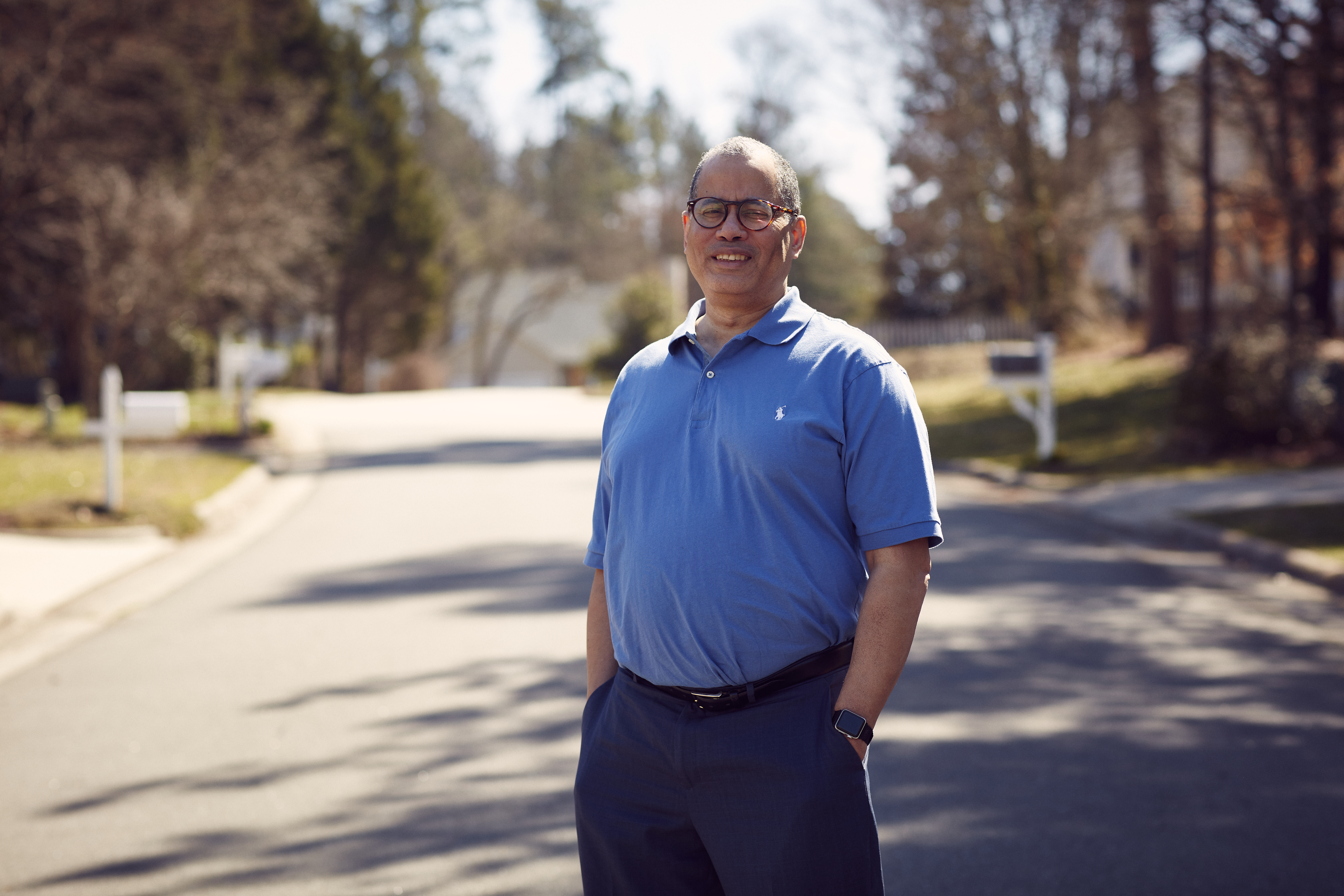 Paul Miller stands in his neighborhood street, smiling, with his hands in his pockets