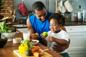 African American man holds his young child in his lap and smiles. The child holds an apple in front of a table full of fresh produce