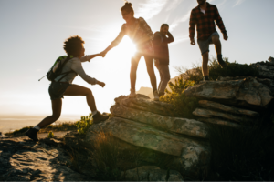 Group of hikers on a mountain at sunset. Woman helping her friend to climb a rock.