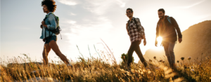 Group of friends hikes across a meadow at sunset