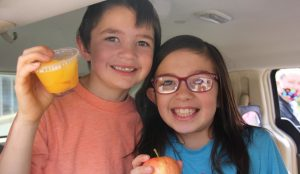 Two children hold up fruit from school lunches and smile