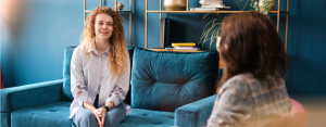 Woman sits on blue velvet couch and smiles at her therapist