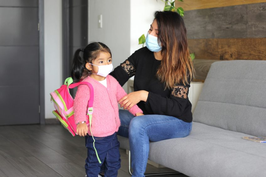 Mom puts on young daughter's backpack, both of them wearing masks.