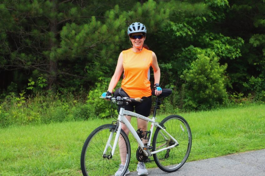 Michelle stands with her bike and smiles