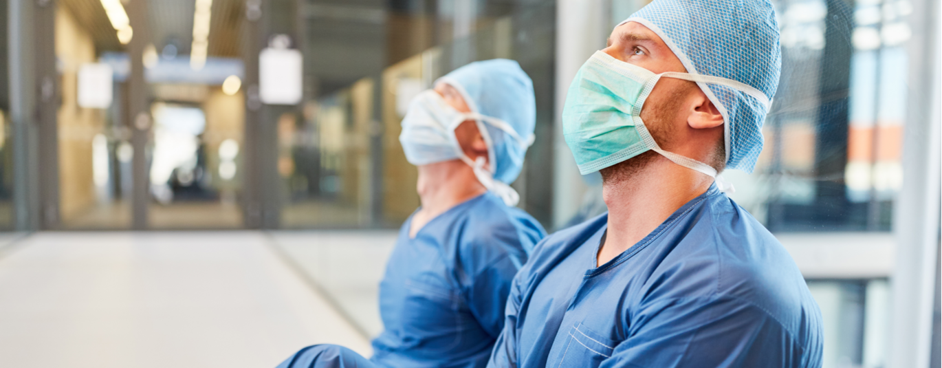 Two exhausted surgeons in blue surgical clothing as a sign of stress and fatigue