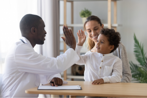 Child on mom's lap high-fives doctor