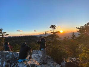 Hikers gather at the rocky summit of a mountain at sunset