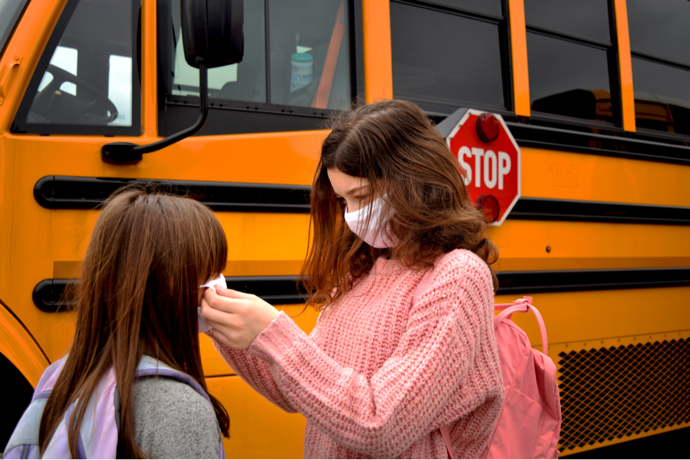 Older student helps younger student put face mask on in front of school bus