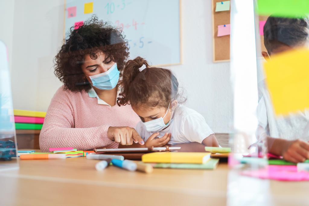 Teacher using tablet with children in preschool during coronavirus outbreak
