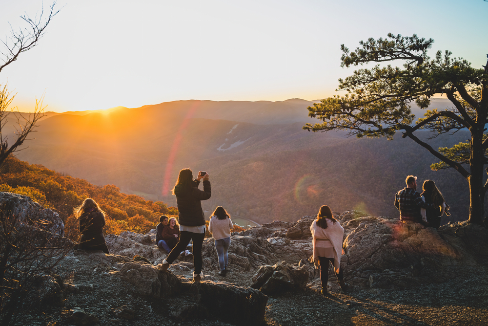 Hikers gather at the top of a mountain at sunset