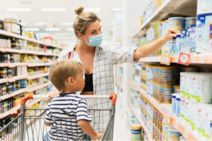 Woman wears mask in grocery store while shopping with her toddler son