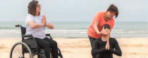 Group of women (one seated in wheelchair, the other seated on the ground) practicing meditation at the beach