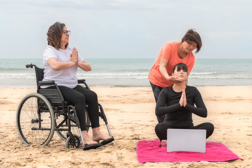 Group of women practicing meditation at the beach