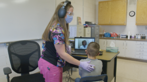 School nurse and little boy do a telehealth visit with a doctor on the computer