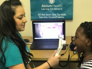 School nurse points camera into young student's throat, and the image appears on a laptop screen