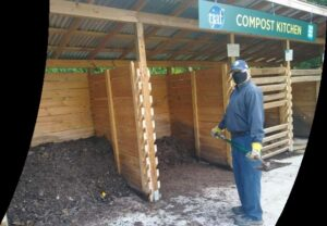"""Man shovels compost at the """"Compost Kitchen"""" outdoors"""