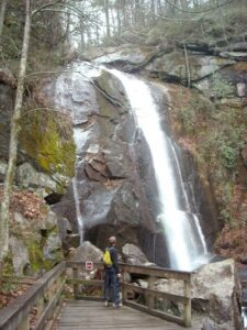 Man stands on a bridge next to a waterfall and looks up