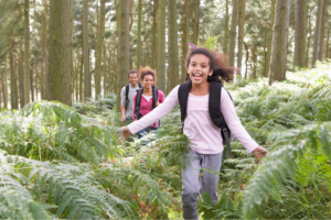 young girl runs ahead of parents on a hike in the forest