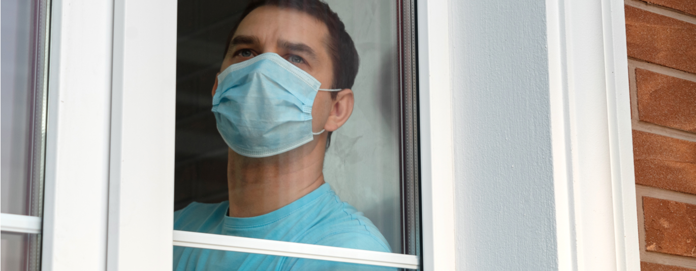Man in a medical mask looks out the window of his home, where he is quarantined.
