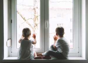Two young siblings in quarantine sit on windowsill with their hands on the window looking out