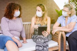 Three women in masks have serious conversation