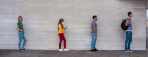 Group of young people stand in line six feet apart