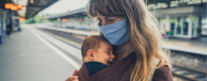 A young mother with her baby in a sling is wearing a face mask at a train station