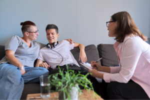Mom puts her arm around teenage son in therapy session