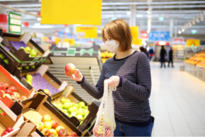 Young woman wears face mask while shopping for groceries