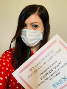 Jennifer Grady holds up her certificate of completion of radiation therapy