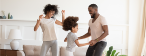 African American family (mom, dad and young daughter) dance around their living room