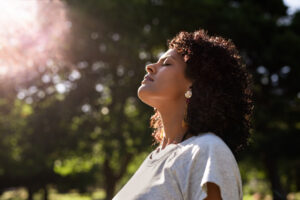young woman tilts her head up toward the sky basking in the sun