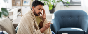 Man sick at home under a blanket, looking at a thermometer