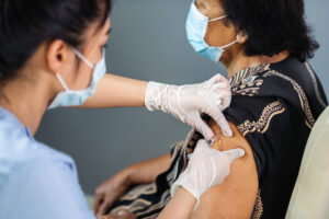 Nurse gives vaccine to older woman