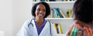 African American female doctor talking about recovery to patient at hospital